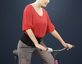 Dominica A Female Model in A Red Blouse Riding A Bicycle
